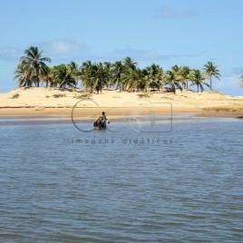 Laguna com dunas e coqueiros ao fundo