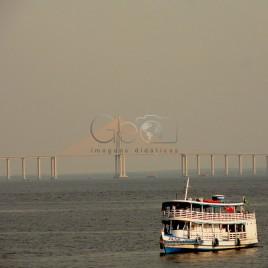 Barca com a ponte Rio Negro ao fundo