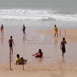 Garotos jogam futebol na praia