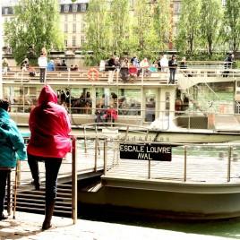 Turistas observam embarcação no Rio Sena